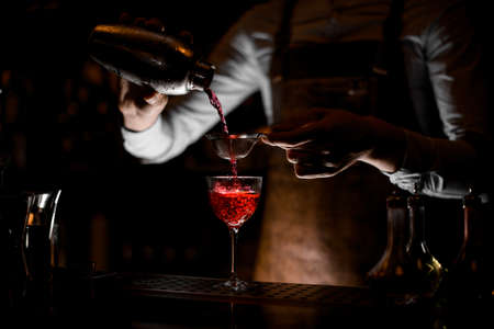 Bartender flows alcohol through sieve in glass