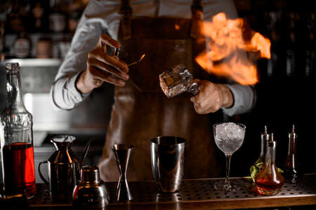 Bartender fires up an ice cube in tongs