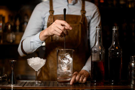 Bartender stirs alcohol cocktail with special spoon