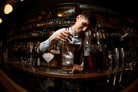 Bartender stirs alcohol drink with special spoon
