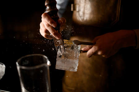 Close-up of bartender crushing the ice cube Stock Photo