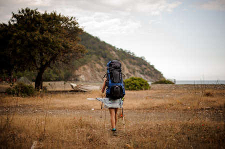 Back view girl with backpack and hiking sticks walking through the field Imagens