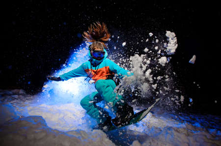 Active female snowboarder dressed in a orange and blue sportswear performs tricks on the snow Imagens