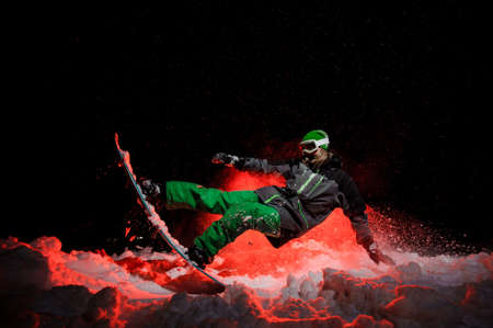Female snowboarder dressed in a green sportswear performs tricks on the mountain slope