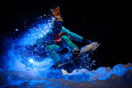 Female snowboarder dressed in a orange and blue sportswear performing tricks on the snow