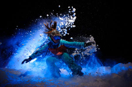 Active female snowboarder dressed in a orange and blue sportswear makes tricks on the snow