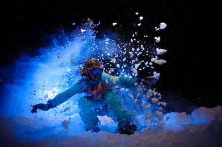 Female snowboarder dressed in a orange and blue sportswear makes tricks on the snow