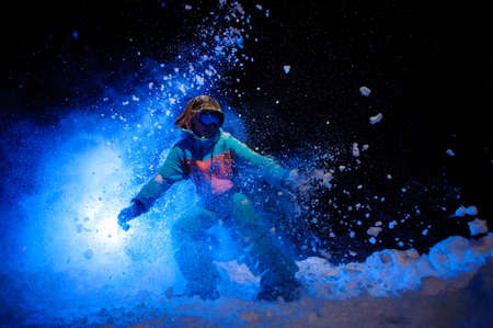 Active female snowboarder dressed in a orange and blue sportswear making tricks on the snow Stok Fotoğraf