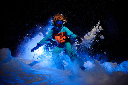 Active female snowboarder dressed in a orange and blue sportswear performing tricks on the snow 写真素材