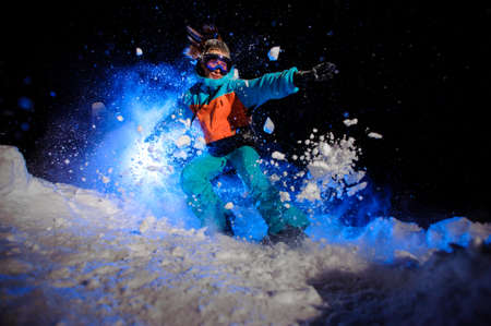 Female snowboarder dressed in a orange and blue sportswear making tricks on the snow