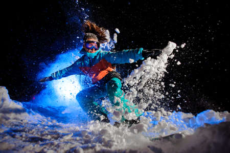 Snowboarder girl dressed in a orange and blue sportswear making tricks on the snow