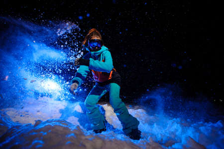 Active female snowboarder dressed in a orange and blue sportswear riding on the snow slope