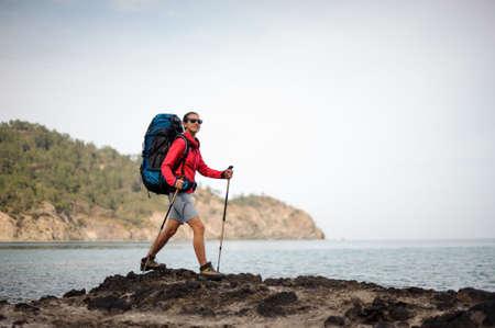 Female traveller in sunglasses walks near the sea Stok Fotoğraf