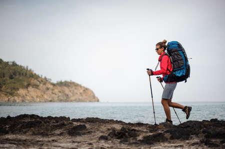 Female traveller in sunglasses walking near the sea