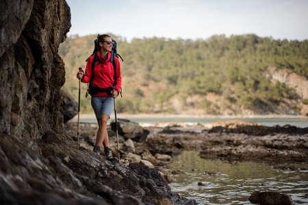 Female traveller walks in front of cliffs Stok Fotoğraf