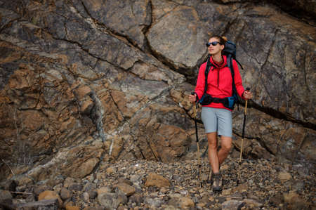 Hiker girl in sunglasses with backpack in mountains Stok Fotoğraf