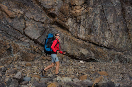 Female traveller walking in front of cliffs