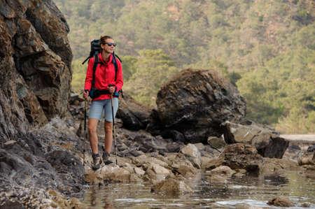 Female traveller in sunglasses walking near the cliff
