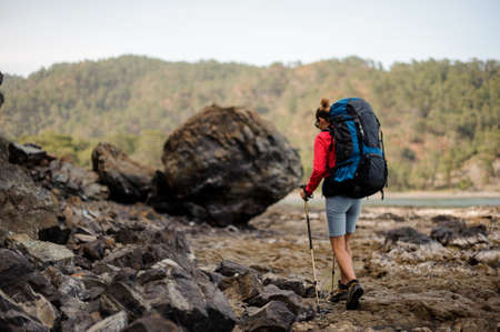 Female traveller with backpack walking near the sea