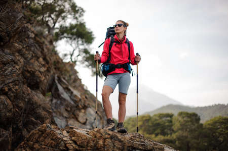 Traveller girl in sunglasses with backpack in mountains