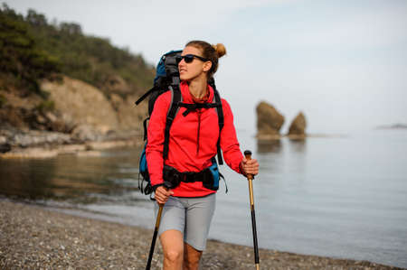Portrait of smiling girl with hiking equipment Фото со стока