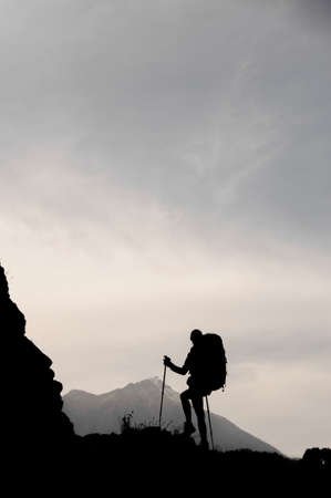 Silhouette woman standing on the rock with hiking backpack and walking sticks