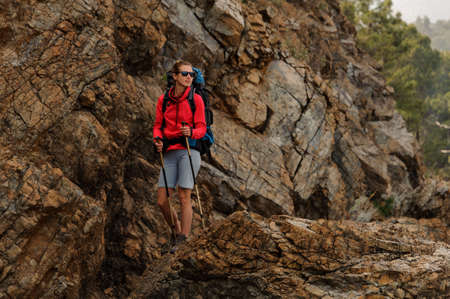 Smiling girl standing on the rocks with hiking backpack and walking sticks