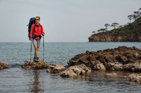 Girl in sunglasses standing on the rock on the sea with hiking backpack