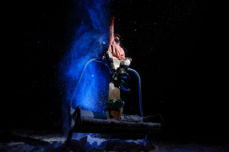Male snowboarder dressed in a white and pink sportswear sitting on the funicular seat rising hand Imagens