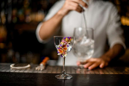 Bartender stirring a cocktail with a spoon in the focus foreground of flower decorated glass Reklamní fotografie