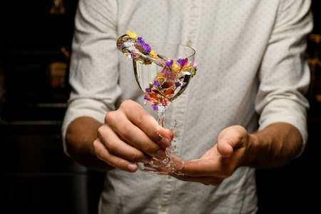 Bartender making a splash with a cocktail in the glass decorated with flowers Standard-Bild