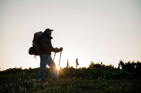 Man standing on the hill field with hiking backpack and sticks
