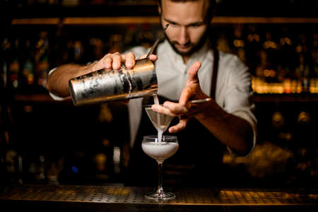 Male bartender pouring a white cocktail from the steel shaker to the glass through the sieve