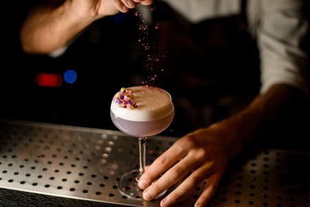 Professional bartender sprinkling on the cocktail with white scum decorated with flower petals a shredded flowers
