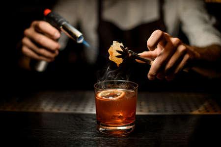 Male bartender serving a brown cocktail melting caramel with a burner above the lemon slice in the dark