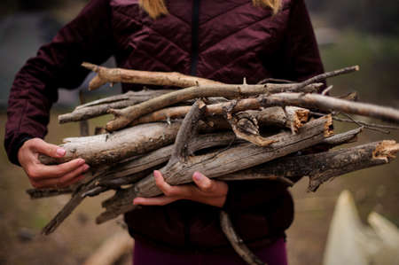 Girl holding in hands a bundle of firewood