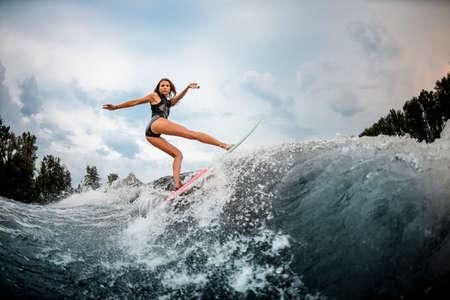 Girl wakesurfer makes stunts on a board
