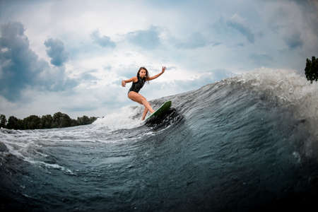 Young girl wakesurfing on a board in the river near forest Stock Photo
