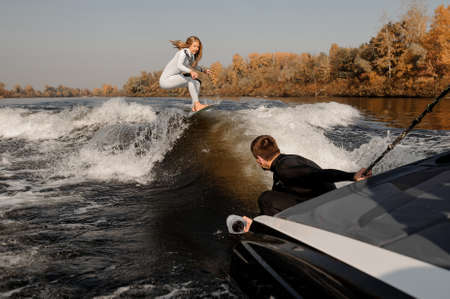 Photographer taking pictures with a camera in moisture proof cover from the motorboat holding the rope of the girl riding on the wake surf