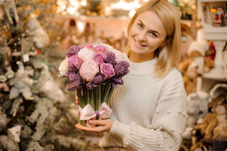 Smiling girl holding a bouquet of tender pink and purple color flowers with green stalks