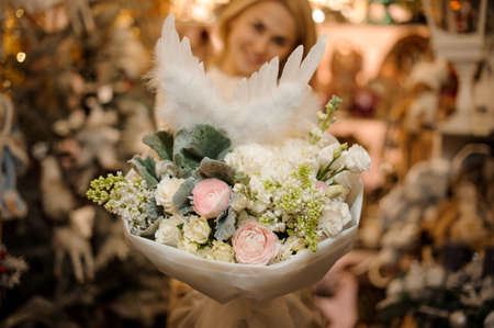 Smiling girl holding a bouquet of tender color roses decorated with green leaves and white feathers