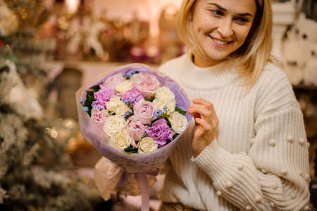 Girl holding a little bouquet with purple and white flowers wrapped in gift paper
