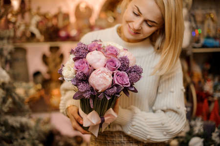 Smiling woman holding a bouquet of tender pink and purple color flowers with green stalks