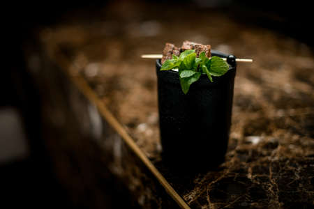 Alcoholic cocktail in the black cup decorated with a brownie pieces on a skewer and mint branch