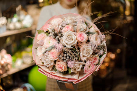 Woman holding a bouquet of pink and beige color roses with a decor of feathers and dry berries