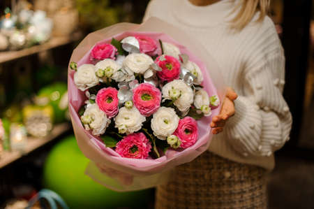 Woman holding a bouquet of bright pink and white peony roses decorated with a green leaves Reklamní fotografie - 133067014