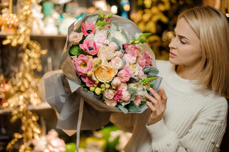 Young woman holding a bouquet of white, yellow and pink flowers decorated with a green shoots of plants Stock fotó