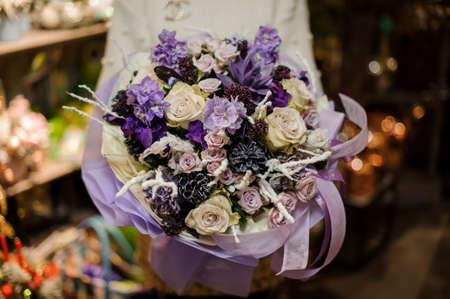 Woman holding a bouquet of purple and creamy flowers decorated with a dark cones