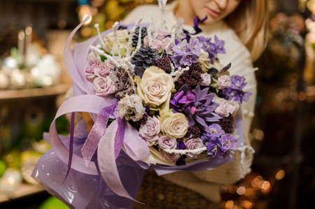Girl holding a bouquet of purple and creamy flowers decorated with a dark cones