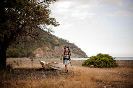 Woman with backpack walking on the dry field near the broken boat Reklamní fotografie